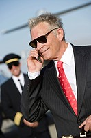 Mid_adult businessman talking on phone airline pilot standing in background.