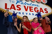 Two women and two men posing in front of Welcome to Las Vegas sign group portrait