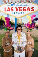 Female dancers and Elvis impersonator posing in front of Las Vegas welcome sign Nevada USA
