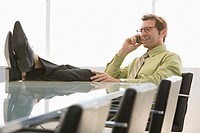 Business man using mobile phone in conference room (thumbnail)