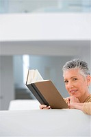 Middle_aged woman reading book on sofa