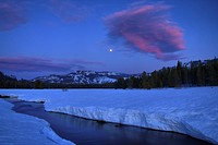 The full moon rising over a stream near Lake Van Norden near Soda Springs in California