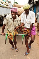 Men joking with each other as they pull a cart down the street  Kollam, Kerala, India