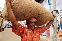 A porter carrying a large bag of shallots on his head  Kollam, Kerala, India