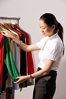 Chinese fashion designer selecting clothes from rack