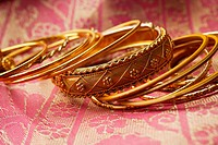 gold Indian bangles on pink sari cloth