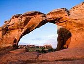 Sunrise illuminates Broken Arch framing sandstone fins in background, Arches National Park, Utah, USA