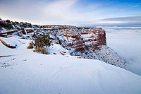 Red rock canyons are covered in a layer of snow as fog rolls in below the plateaus in Canyonlands National Park