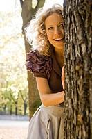 Woman hiding behind tree