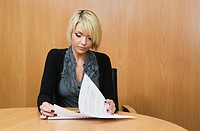 Woman looking at papers in boardroom