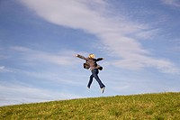Man jumping into distance on grass
