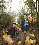 Boys throwing autumn leaves
