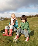 Girl and boy with toy planes in field