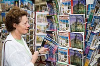 Tourist selecting Barcelona guidebook, La Rambla, Barcelona, Spain