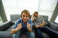 Two men sitting on sofa watching television, one cheering, other holding head