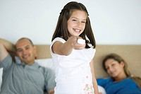 Girl holding out remote control, smiling at camera, parents in background