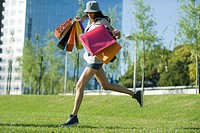 Young woman running through park, carrying several shopping bags