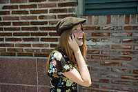 Young woman wearing trendy hat and talking on cell phone