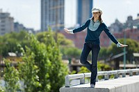 Young woman in trendy clothing standing on one leg on ledge