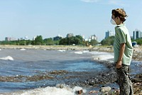 Boy wearing pollution mask, standing on polluted shore