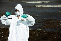 Person in protective suit testing polluted water