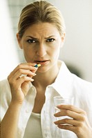 Woman holding pill, frowning at camera