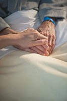 Nurse holding elderly man's hand