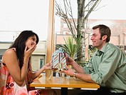 Man giving woman gift in restaurant