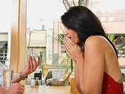 Man giving girlfriend engagement ring in restaurant