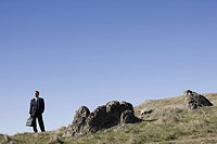 Businessman standing on remote hill