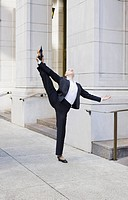 Businesswoman stretching on urban sidewalk