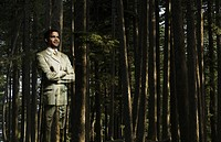 Businessman standing in a forest