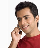 Close_up of a young man talking on a mobile phone and smiling