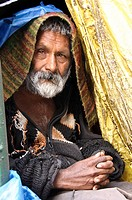 Mentally disabled man sitting in his makeshift home on the street McLeod Ganj, Himachal Pradesh, India