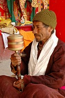 A man using a hand prayer wheel at the festival of Lama Yuru monastery Ladakh, India