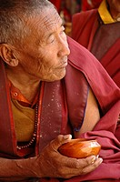 Older monk holding a cup of tea Lama Yuru, Ladakh, India