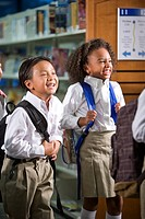 Asian and African American elementary school children laughing in library