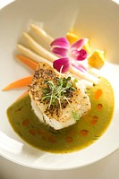 Close_up of gourmet meal of white fish and vegetables with floral garnish