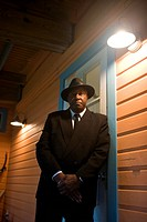 Portrait of senior African American man in suit and hat leaning against porch door at night