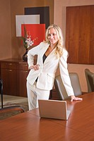 Portrait of young fashionable businesswoman in boardroom with laptop
