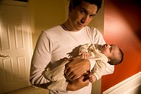 Portrait of father holding baby boy in his arms at home