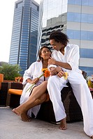 Portrait of romantic African American couple sitting on rooftop terrace in city