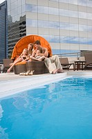 Portrait of family lounging poolside on rooftop terrace in the city