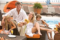 Portrait of happy family lounging poolside on rooftop terrace in the city