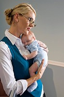 Portrait of young businesswoman holding sleeping baby at work