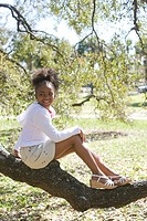 Portrait of African American girl sitting on tree branch in park