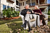 Portrait of senior couple in yard of luxurious home