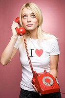 A young woman holding a telephone