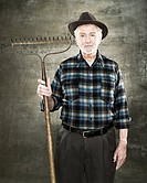 Portrait of a farmer holding a rake