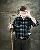 Portrait of a farmer holding a rake